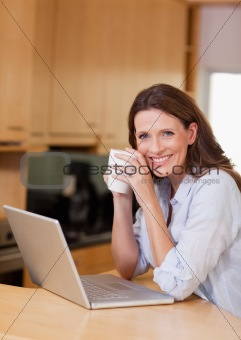 Woman with cup next to laptop