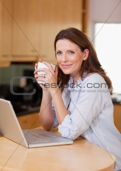 Woman with laptop and a cup
