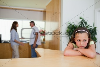 Sad girl listening to fighting parents