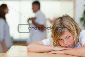 Sad looking boy with fighting parents behind him