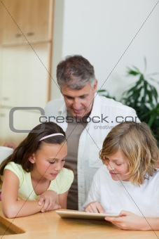 Boy with tablet showing things to sister and father