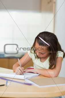 Girl writing in the kitchen