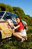 Attractive pinup girl washing a car at summer
