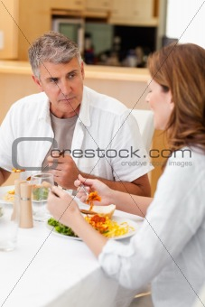 Man talking to wife during dinner