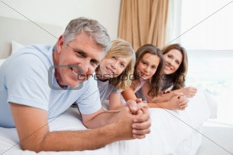Cheerful family lying on the bed