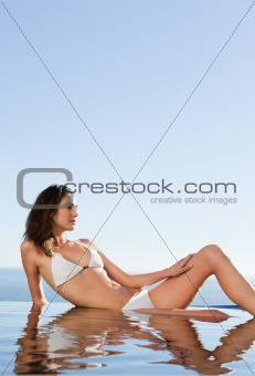 Woman enjoying the sun on pool edge