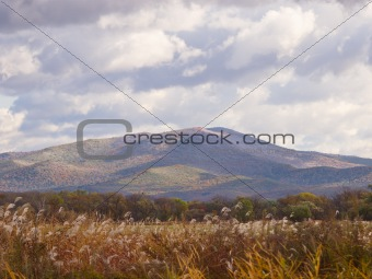 Autumn landscape with mountain and the cloudy sky