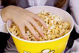 hand in a bucket of popcorn