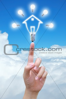 light bulb model of a house in hand on sky
