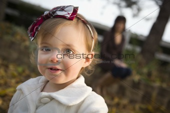 Adorable Baby Girl Playing Outside in the Park with Mom Behind Her.