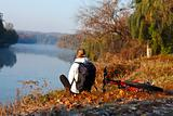 Woman cyclist enjoy the recreation on the river-side