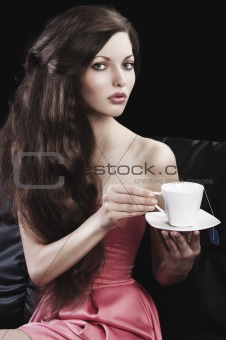 sophisticated lady drinkig tea, she takes a cup of tea with both