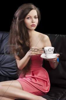 sophisticated lady drinkig tea, she takes the cup with both hand