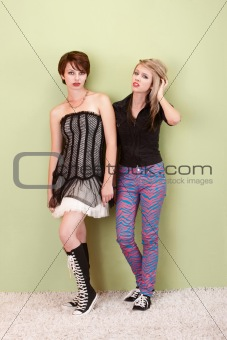 Two frustrated punk teen girls look to the camera