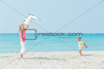 girl with brother on beach playing with a kite