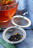 tea strainer with a fragrant black tea and cups in the background