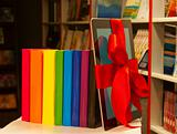 Electronic book reader tied up with red ribbon and row of books