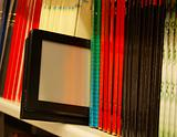 Row of colorful books and electronic book reader on the shelf