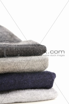 A pile of warm knitted gray sweaters