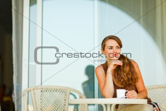 Thoughtful woman sitting on terrace and having cup of coffee