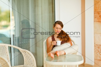 Calm beautiful woman relaxing on terrace with cup of coffee