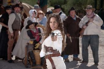 Defiant cowgirl pointing gun.