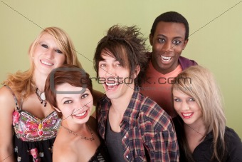 Five laughing urban teens in front of green wall