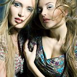 Fashiong portrait of two beautiful women with streaming hair loo