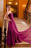 woman in a beautiful dress sloit on the stairs