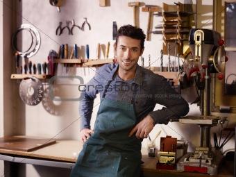 Happy italian artisan at work, smiling in guitar workshop
