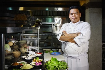 asian chef smiling at camera in restaurant kitchen