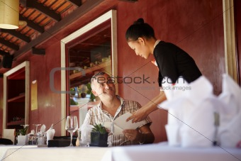 asian waitress talking with client in restaurant