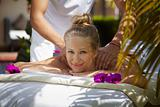Happy young woman smiling during massage in spa