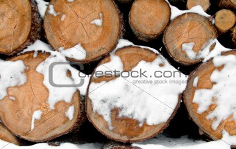Log stack lumber with snow