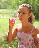 Portrait of the pretty little girl blowing bubbles