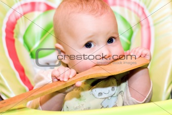 baby biting a wooden spoon