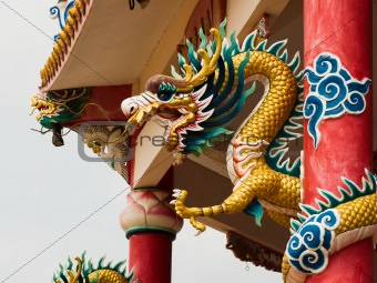 Right Golden gragon statue on red pillar