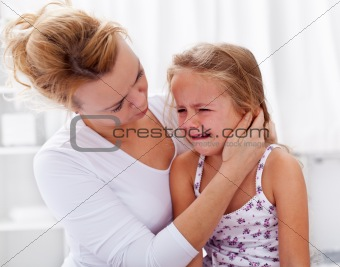 Mother comforting her crying little girl