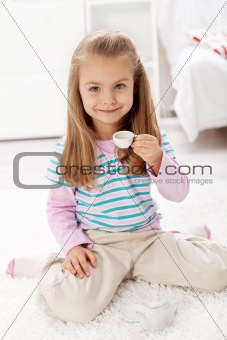 Litlle girl having tea