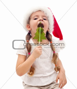 Little girl with a christmas tree shaped candy