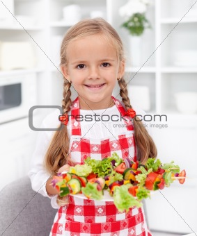 Happy girl with vegetables plate