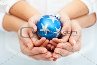 Adult and child hands holding christmas bauble