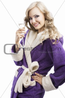 blond happy girl in bathrobe drinking champagne, she looks in o