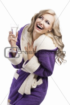 blond haooy girl in bathrobe drinking champagne, she laughs and