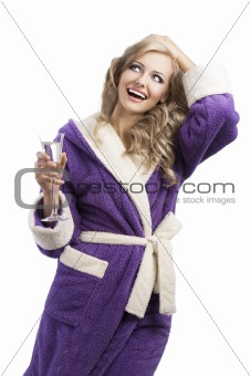 blond hoody girl in bathrobe drinking champagne, she looks up an