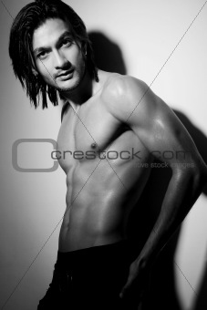 Portrait of a young Indian shirtless male posing with hand on hip.
