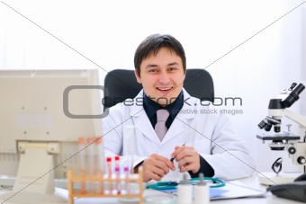Smiling medical doctor sitting at table in office