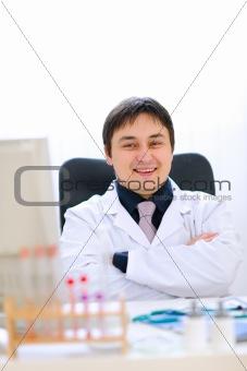 Portrait of smiling medical doctor sitting in cabinet