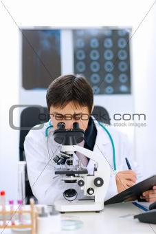 Researcher using microscope in medical laboratory