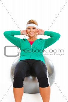 Fitness girl making abdominal crunch on fitness ball isolated on white